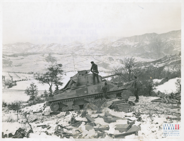 "South African tank men, probably of the South African 6th Armored Division, with M4Al Sherman tank on hilltop; shells are being loaded in through turret. ""28 Dec. 1944. 5/MM-44-32547. Fifth Army, Monzuno Area, Italy. These South African tank men fight for the first time in snow country, in the rugged Apennines. Against the snow-clad mountains this tank is made ready for firing. Photo by Schmidt. 3131 Signal Service Co."" Near Monzuno, Italy. 28 December 1944 From the Digital Collection of the US National WW2 Museum"